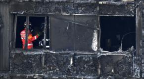 Des pompiers inspectent ce qu'il reste de la tour Grenfell ravagée par un incendie.