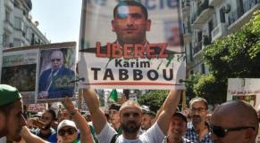 Un protestataire tenant un panneau réclamant la libération de Karim Tabbou lors d'une manifestation à Alger, en 2019 (Afp).